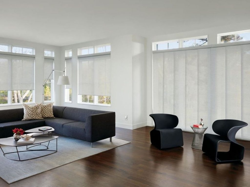 Panel track window treatments cover the many windows in an open room.